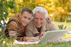 Boy and grandfather with  laptop Stock Images