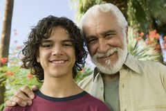 Boy (13-15) with Grandfather outdoors front view portrait. stock photos