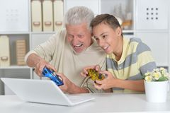 boy and  grandfather playing computer game Stock Images
