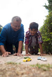 Boy and grandfather playing with toy cars against sky Royalty Free Stock Photo