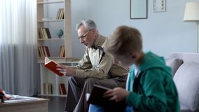 Boy and grandfather reading books, concept of education available at any age stock photos