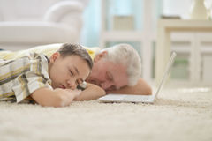Boy and  grandfather sleeping near laptop Royalty Free Stock Photography