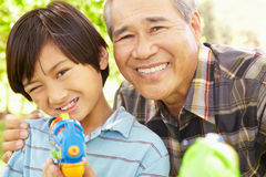 Boy and grandfather with water pistols Royalty Free Stock Images