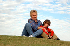Boy and grandma. A boy and his grandmother sitting together outdoors on a hill Royalty Free Stock Photos