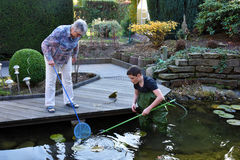 Boy and grandmother cleaning garden pond Royalty Free Stock Images