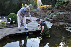 Boy and grandmother cleaning garden pond Royalty Free Stock Photography