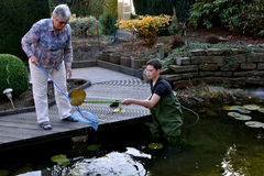 Boy and grandmother cleaning garden pond Stock Image