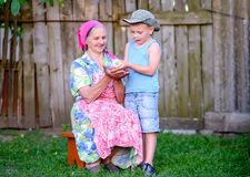 Boy with Grandmother Holding Young Chick Outdoors Royalty Free Stock Photography
