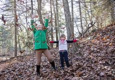Boy and grandmother playing in leaves. A boy and senior women throwing leaves up in the air in Autumn royalty free stock images