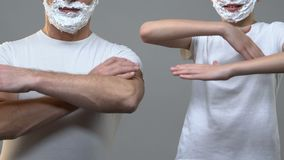 Boy and grandpa with hands crossed and shaving foam on faces, men traditions