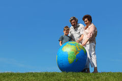 Boy and grandparents looking on big globe Stock Image