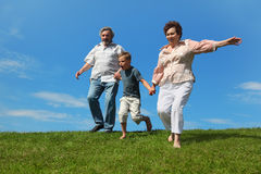 Boy and grandparents running on summer lawn Stock Photography