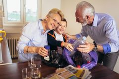 Boy with grandparents separating recyclable trash. At home stock photography