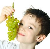 Boy with grapes Stock Images