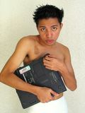 Boy grasping laptop. Asian boy frowning, grasping laptop PC royalty free stock photos