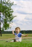 Boy on the grass. The boy sits on a grass Royalty Free Stock Images