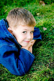 Boy in grass. Cute boy lying in grass and smiling, close-up royalty free stock photography