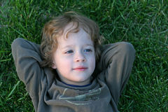 Boy in the grass. A brown haired boy laying in the grass Stock Photos