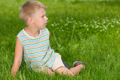 Boy on the grass looking aside Stock Images