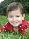 Boy in grass1. A young boy lying in bright green rye grass stock photos
