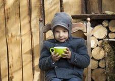 Boy in gray coat drink tea royalty free stock photo