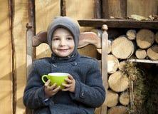 Boy in gray coat drink tea stock images