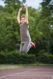 Boy in gray jumpig high. Full body view of a young male teenagers at an air jump on the sports field Royalty Free Stock Photography