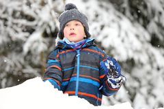 Boy with gray stocking cap and color striped jacket playin on the snow pile Royalty Free Stock Image