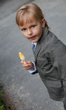 Boy in a gray suit eats ice cream Royalty Free Stock Image
