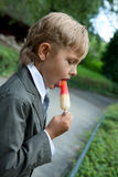 Boy in a gray suit eats ice cream royalty free stock photography