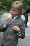 Boy in a gray suit eats ice cream Stock Images