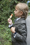 Boy in a gray suit eats ice cream Stock Image