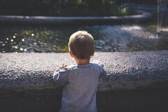 Boy in Gray Top Standing in Front of Water Fountain Royalty Free Stock Image