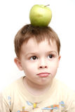 The boy with a green apple. On a head Royalty Free Stock Photography