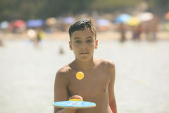 Boy with green eyes playing tennis on the beach Royalty Free Stock Photos