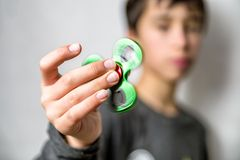 Boy with fidgets spinner in hand. Boy with green fidget spinner in hand stock photo