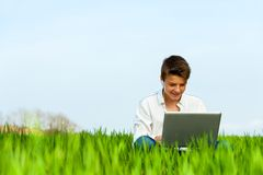 Boy in green field with laptop. royalty free stock images