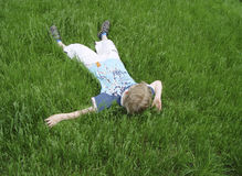 Boy on the green grass. Boy lying on the grass stock photos