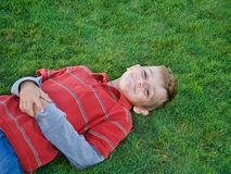 Boy on green grass. Young boy enjoying the summer heat on the cool green grass Royalty Free Stock Photos