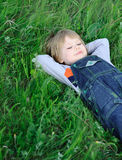 The boy on a green grass Royalty Free Stock Image