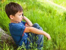 Boy in green grass talking on cell phone Royalty Free Stock Photos