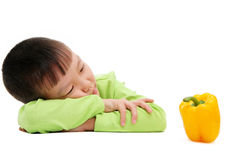 Boy in green looking at yellow bell pepper Stock Images