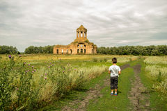 Boy in green meadow with church on a backgroung. Little child looking at the ancient church in green meadow stock photos