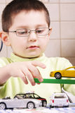 Boy in green playing with cars Royalty Free Stock Images