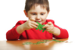 Boy with green puzzles Stock Photos