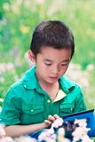 A chinese boy reading iPad. A relax time in Beijing Olympic Forest Park Stock Photo
