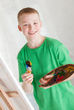 Boy in green shirt holding painters pallet Royalty Free Stock Photos