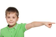 Boy in green shirt shows her finger to the side Stock Images