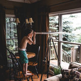 Boy in Green Shorts Near Grey Telescope during Daytime Stock Images