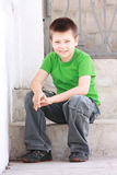 Boy in green sitting on steps Stock Photos